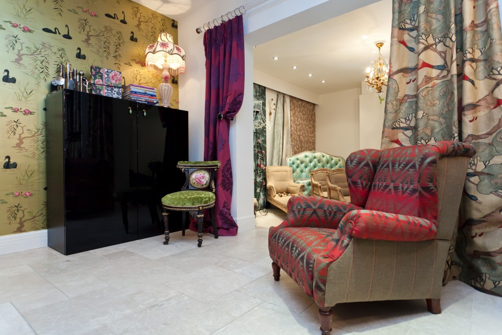 French armchair covered in fabrics from Andrew Martin. Sitting in front of a curtain made with Mulberry's flying ducks