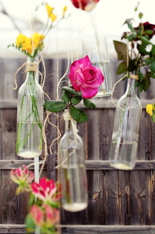 Single flower stems in hanging bottles