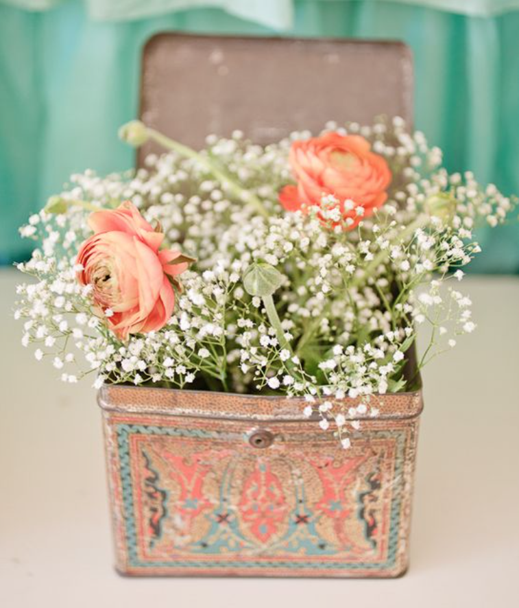 Floral display in an open vintage tin box
