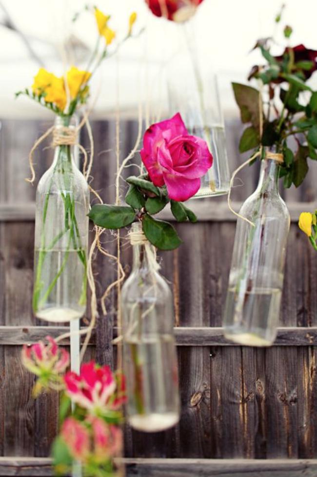 Single flower stems in hanging bottles
