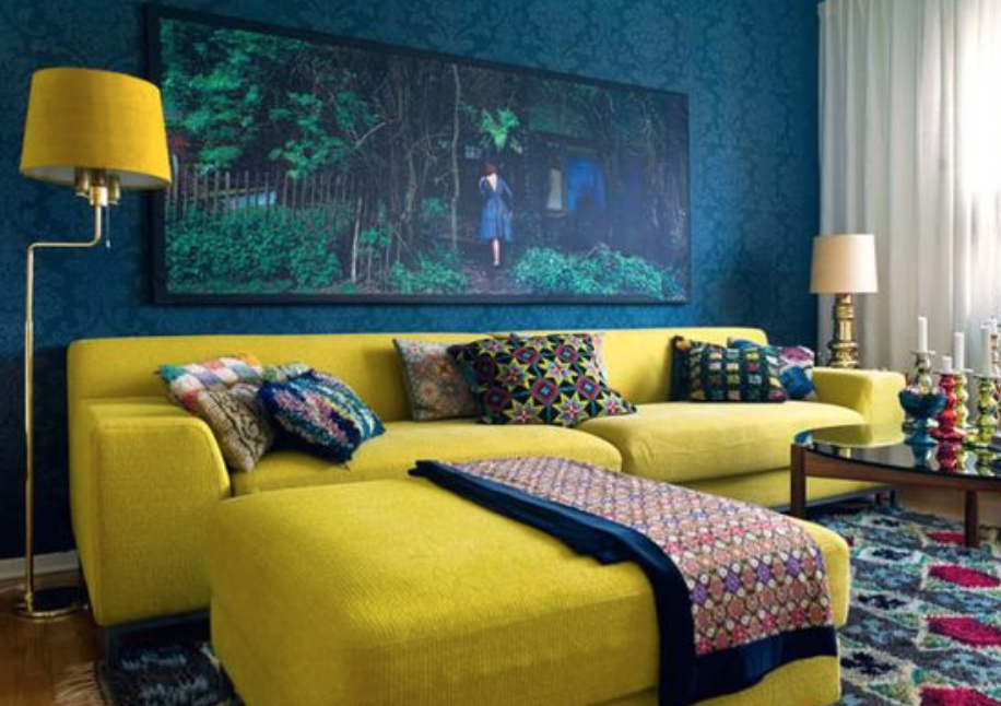 Yellow sofa and footstool in dark blue living room