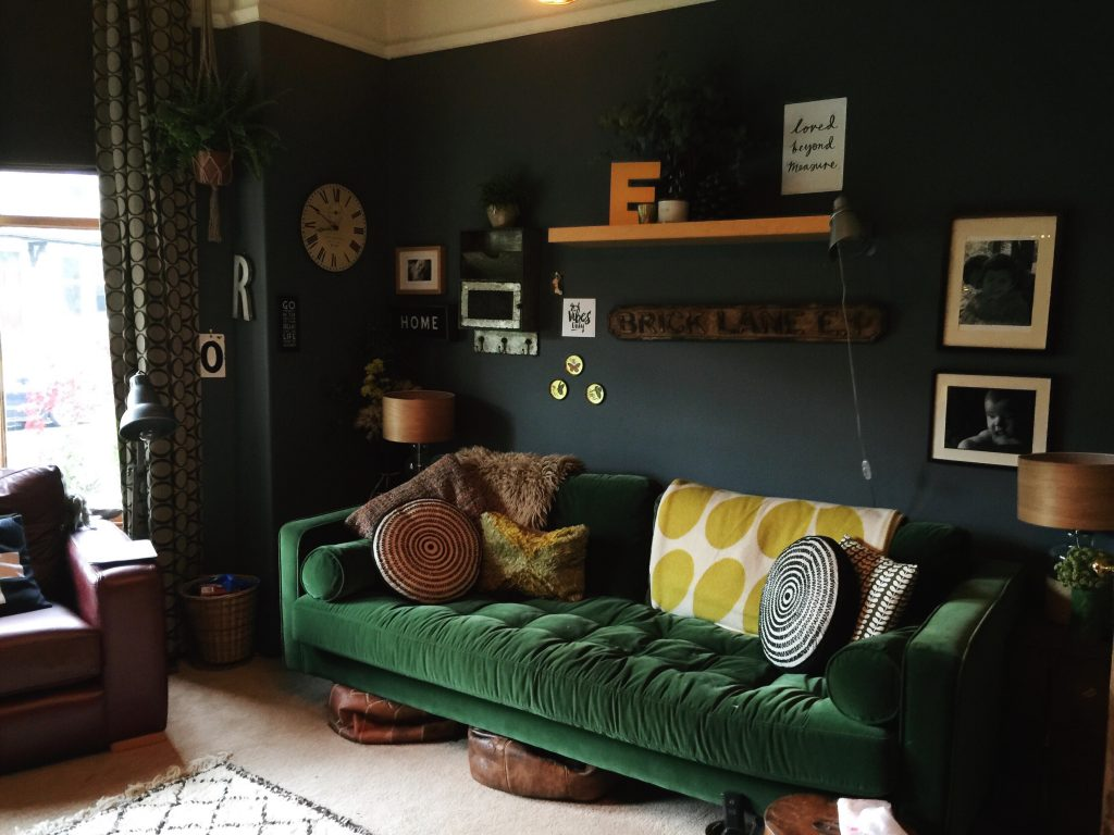dark living room with green velvet sofa